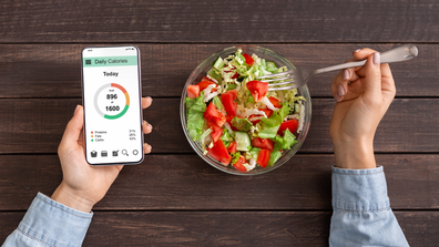 Woman counting calories on app and eating a salad