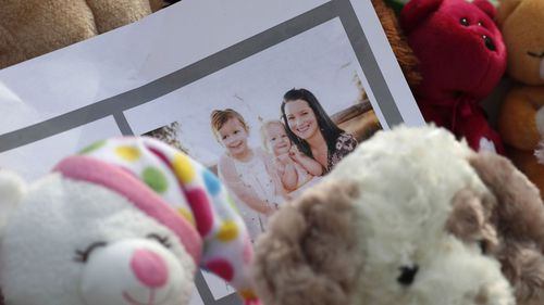 A photograph sits amid the tributes as they grow outside the home where a pregnant woman, Shanann Watts, and her two daughters, Bella and Celeste, lived. (AAP)