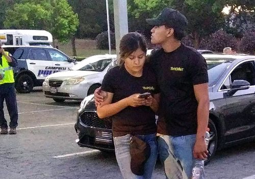 A young couple embrace at a parking lot after a shooting at the Gilroy Garlic Festival