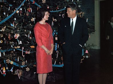 John F. Kennedy and Jackie Kennedy pose with the White House Christmas tree in 1961.