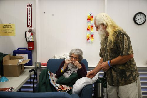 Evacuee Steve Clapper tells his mother, Euteva Bukowiecki, to wear an oxygen tube at a shelter in Pahoa. (AAP)