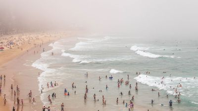 Over the harbour at Manly Beach, sunbathers at South Steyne could barely see the Queenscliff pavilion to the north. (Photo: Diimex)