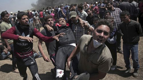Palestinian protesters carry an injured man who was shot by Israeli troops during a deadly protest at the Gaza Strip's border with Israel