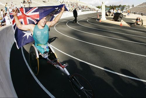 Fearnley pulls the Australian flag over his head after winning the Mens Marathon (T54) at Panathinaiko Stadium during the 2004 Paralympic Games in Athens, Greece. (Getty)
