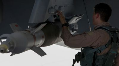 An Australian Air Combat officer performing a pre-flight check on his aircraft. (Picture: ADF)