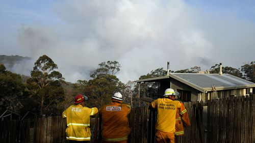 NSW Rural Fire Service crews watch on as the Morton Fire burns in bushland close to homes at Penrose in the NSW Southern Highlands, 165km south of Sydney, Friday, January 10, 2020