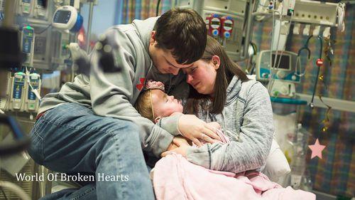 Adalyn is cradled by her parents in hospital. (World of Broken Hearts / Facebook)