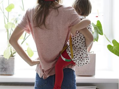 Mother standing at window holding toddler