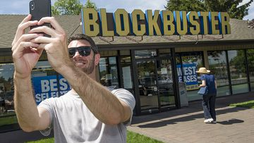 A man takes a selfie outside the Ben, Oregon Blockbuster store. It will be the last one in the world after an announcement Australia's last one is closing. (Ryan Brennecke)