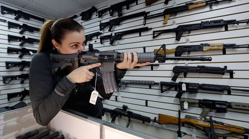 Gun shop owner Tiffany Teasdale-Causer points a Ruger AR-15 semi-automatic rifle