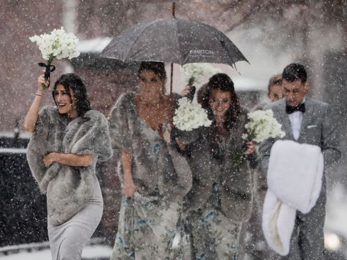 A bridal party battles the cold weather. (Image: AAP)