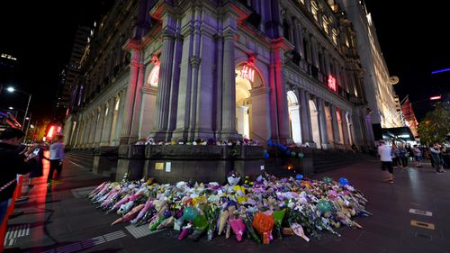 Members of the public light candles and leave flowers late into the evening on the corner of Bourke and Elizabeth Street