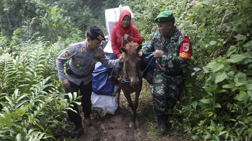 A police officer and a soldier assist a worker as they use horses to distribute ballot boxes and other election paraphernalia to polling stations in remote villages in Tempurejo, East Java, Indonesia.