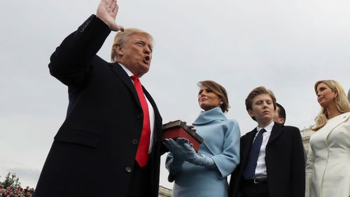Donald Trump holds hand on bible during inauguration.