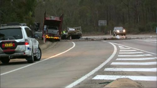 A driver has been killed and another person trapped in the wreckage of a vehicle during a two-truck collision on Picton Road in Wilton, in Sydney's south-west.