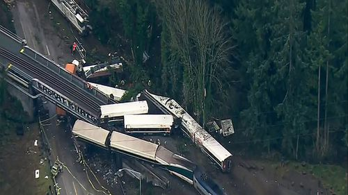 "A passenger train is dangling over a motorway in the US, with fears it may be a ""mass casualty incident"". (AAP)"
