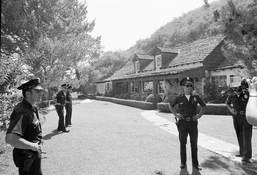Police officers stand on the property of actress Sharon Tate where the bodies of five persons, including Tate, were found murdered by members of the Manson cult family, August 9, 1969.