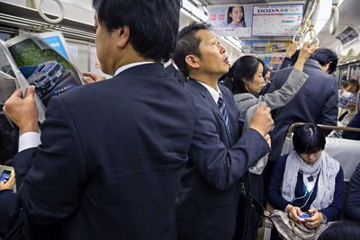 A moment of thoughts on the way to the office, in the Tokyo subway (Japan, 2015).