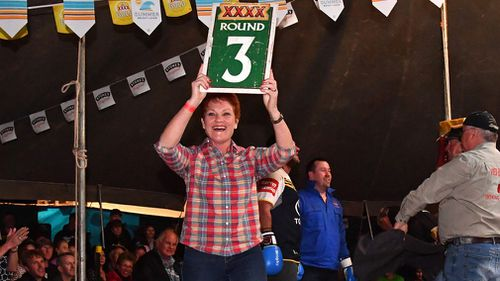 Senator Pauline Hanson acts as the ring girl during the boxing at the Fred Brophy's Boxing Tent in Birdsville. (AAP)