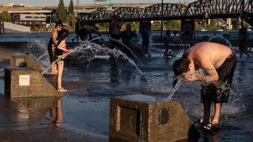 A boy cools off in a riverfront water fountain during a heatwave in Portland, Oregon, USA.
