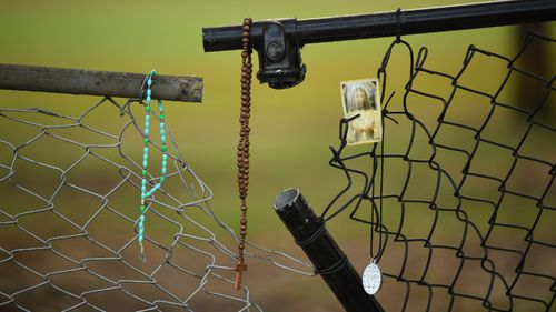 Rosaries at the section of fence where the children were killed.