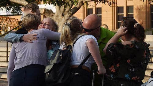 People embrace returning family members in Circular Quay.