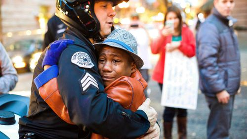 Portland police Sgt. Bret Barnum, left, and Devonte Hart, 12, hug at a rally in Portland.
