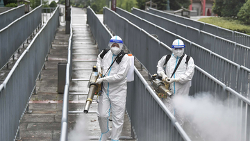 Workers spray disinfectant to halt the spread of COVID-19 on August 26, in Zhangjiajie, Hunan Province of China.