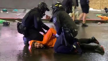 A suspected looter is pinned to the ground by two police officers, including one who uses his knee to hold the man to the ground.