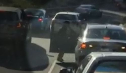 The woman approaches the other drivers car before opening the door and leashing out. Picture: Supplied
