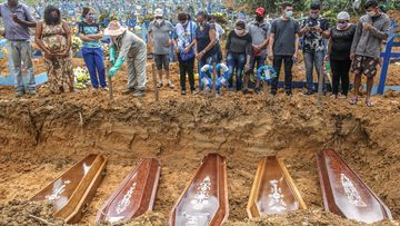 People wearing protective masks observe to the graves with the remains of their relatives during a mass burial of coronavirus  pandemic victims at the Parque Taruma cemetery