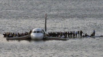 Passengers wait to be rescued on the wings of a US Airways plane that safely landed on the Hudson River in New York on January 15, 2009.