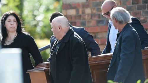 Ex-wife of the late Carl Williams, Roberta Williams (left) carries the casket as a pall bearer at the funeral for George Williams. (AAP)