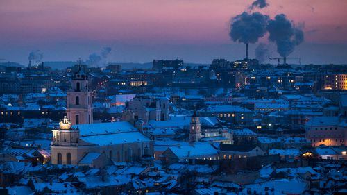 Smoke rises from chimneys during a freezing winter evening over snow covered Vilnius, Lithuania. (AP).