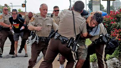 Police tackle a man who was walking down the street in front of McDonald's on Monday in Ferguson. The man appeared to be walking past a group that had been assembled nearby and police were telling everyone to keep walking. Moments after he turned around and exchanged words with the police that he was just walking, police took him to the ground. (AP)