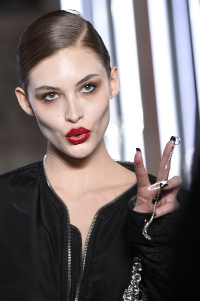 Punk rock nail art (yep, it's a piercing) teamed with a 60's inspired elegant red lipstick for Philipp Plein.