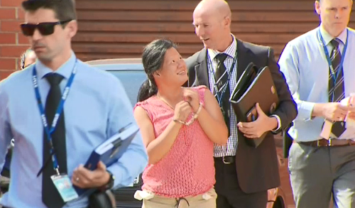The woman smiles at the detective as she's led away. (9NEWS)