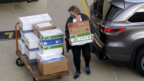Elections officials from across Dane County bring the ballots on Thursday, November 19, 2020, to Monona Terrace in Madison, Wisconsin for the count that begins Friday.