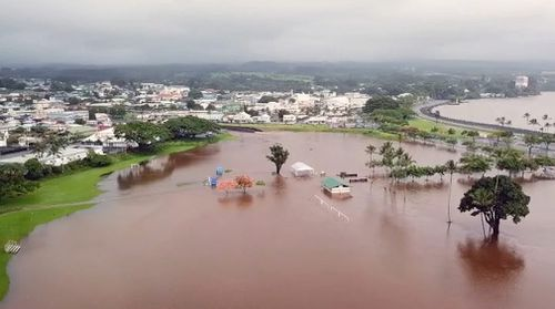 Emergency crews rescued five California tourists from a home they were renting in Hilo after a nearby gulch overflowed and flooded the house.
