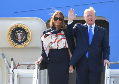 US President Donald Trump tries to hold wife Melania's hand