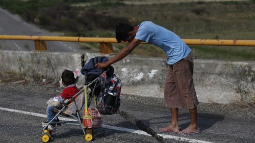 A man pushes a child in a stroller along the highway as a thousands-strong caravan of Central Americans continues its slow journey toward the US border, between Niltepec and Juchitan, in Oaxaca state, Mexico.
