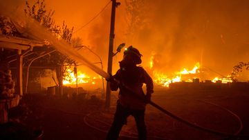 Firefighters are struggling to contain three wildfires near Los Angeles as forecasters warn that the risk of new fires was high with temperatures expected to spike and humidity levels to drop across California.