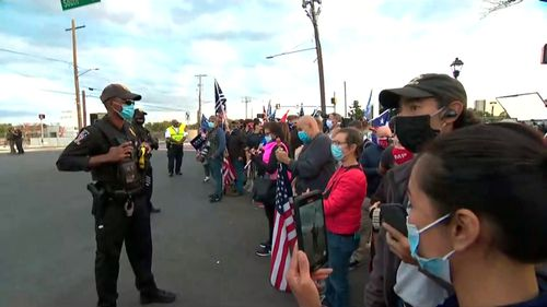 Law enforcement officials stand at a perimeter as Trump supporters gather to wish the President well as he left the hospital today.