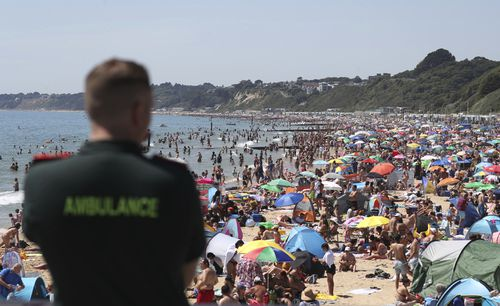 An ambulance officer looks out at people crowded on the beach in Bournemouth, England, on June 25, after coronavirus lockdown restrictions were relaxed.