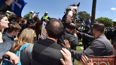 Anti-racism protesters from Campaign Against Racism and Fascism push back police horses during a counter-rally near the anti-Islamic Reclaim Australia group protest in Melton. (AAP)