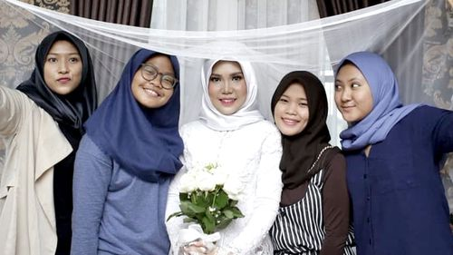 Intan Syari in her wedding dress with friends holding up her veil.
