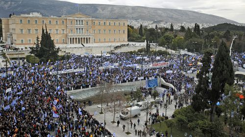 Protesters wave Greek flags outside parliament in Athens, Sunday, Jan. 20, 2019.