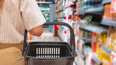 Woman grocery shopping while holding a basket.