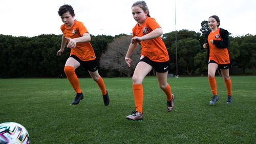 Siblings, Finnair, Elena and Ishbel Collins from the Balmain and District Football Club, having a kick.