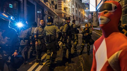 Riot police stand guard on the street during Halloween celebration.